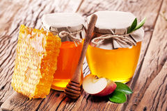 Glass cans full of honey and apple piece and combs. Royalty Free Stock Images