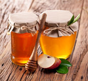 Glass cans full of honey and apple piece. Royalty Free Stock Photos