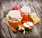 Glass cans full of honey, apples and combs. Royalty Free Stock Images