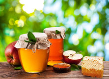 Glass cans full of honey, apples and combs. Royalty Free Stock Photos