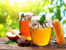 Glass cans full of honey, apples and combs. Glass cans full of honey, apples and combs on old wooden table in the garden Royalty Free Stock Photography
