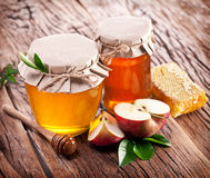 Glass cans full of honey, apples and combs on wood. Royalty Free Stock Photo