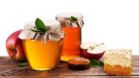 Glass cans full of honey, apples and honeycombs. Clipping paths. Stock Photo