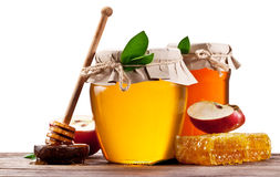 Glass cans full of honey, apples and honeycombs on wood. Clippin Royalty Free Stock Images