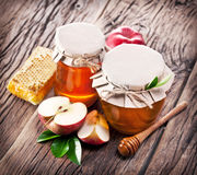 Glass cans full of honey, apples honeycombs on wood. Royalty Free Stock Photos
