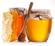 Glass cans full of honey, honeycombs and wooden stick. Royalty Free Stock Photos