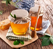 Glass cans full of honey. Royalty Free Stock Images