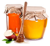 Glass cans full of honey and piece of apple. Stock Photos