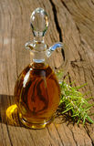 Glass carafe of olive oil. Glass carafe with golden olive oil and a rosemary twig on rustic wooden table Royalty Free Stock Photos