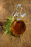 Glass carafe of olive oil. Glass carafe with golden olive oil and a rosemary twig on rustic wooden table Royalty Free Stock Images
