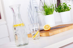 Glass and carafe with lemonade on a kitchen counter Stock Photos
