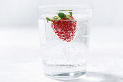 Glass of carbonated water with fresh strawberries. Horizontal Stock Image