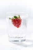 Glass of carbonated water with fresh strawberries, vertical Stock Images