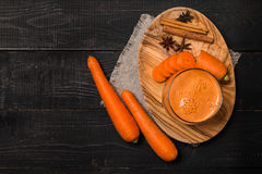 Glass of carrot juice and carrots. On black wooden background, top view Royalty Free Stock Image