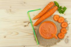 Glass of carrot juice and carrots on the wooden table. Healthy juice full of vitamins and fiber. Diet Food. Stock Photo