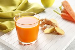 Glass of carrot juice. On white wooden background Royalty Free Stock Image