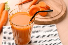 Glass of carrot juice with slices. On table royalty free stock images