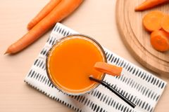 Glass of carrot juice with slices. On table stock image