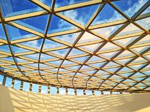Glass ceiling. Curved glass ceiling and blue sky. Pattern of cellular metal construction Royalty Free Stock Photos