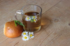 Glass of chamomile tea and a bun Stock Images