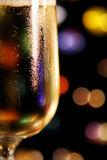 Glass of Champagne. Closeup of a glass of champagne, with colorful lights in the background. Shallow focus on condensation on glass stock photos