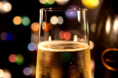 Glass of Champagne #2. Closeup of a glass of bubbling champagne, against multi-colored lights. Bottle in background royalty free stock photo