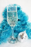 Glass with champagne. Ornaments and a toy on a fur-tree royalty free stock photos