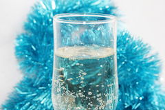 Glass with champagne. Ornaments and a toy on a fur-tree Stock Photos