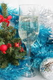 Glass with champagne. Ornaments and a toy on a fur-tree Stock Photography