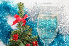 Glass with champagne. Ornaments and a toy on a fur-tree Stock Image