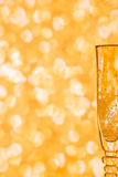 Glass of champagne against blurred golden background. Royalty Free Stock Photography
