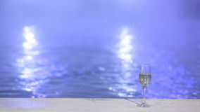 Glass of champagne on the background of night thermal pools stock video