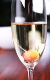 Glass of champagne with a cherry Royalty Free Stock Photos