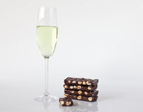 Glass of champagne and chocolate with hazelnuts. On light background stock photos