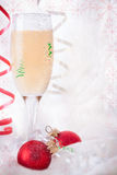 Glass with Champagne and Christmas baubles Royalty Free Stock Photography