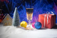 Glass of champagne with Christmas decoration. Traditional winter holiday alcohol drink in snow with creative New Year artwork. stock photos