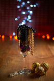 Glass of champagne, Christmas tree decorations and beads Stock Images
