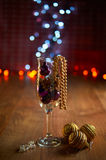 Glass of champagne, Christmas tree decorations and beads Royalty Free Stock Photos