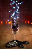 Glass of champagne, Christmas tree decorations and beads Stock Photo