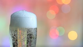 Glass of champagne and colorful defocused new year party background. Glass of pouring champagne and colorful defocused new year party background stock video footage