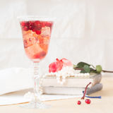 Glass of champagne and cranberry cocktail with vintage books and Stock Photo