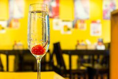 Glass of Champagne drink with cherry in vivid color. Glass of Champagne drink with cherry in vivid color royalty free stock photos