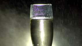 Glass of champagne with falling water drops. stock footage