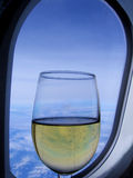 Glass of champagne in front of aircraft window-stock photos Royalty Free Stock Photography