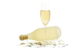 Glass of champagne in front of prosecco bottle wit. Glass of champagne in front of dull prosecco bottle with confetti on white background Stock Image