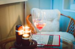 A glass with champagne and lighted candles. Beautiful cozy interior, a place to relax. stock image