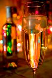 A glass of champagne on lights background. A glass of champagne and abstract lights bokeh background royalty free stock images