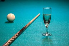 A glass of champagne is on the pool table. the winner of the game, the champion drinks a glass of sparkling wine. Hobbies, sports royalty free stock photo