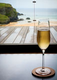 Glass of champagne in Cornwall. Glass of champagne in a resort overlooking the Cornish coastline, beach and cliff royalty free stock photos