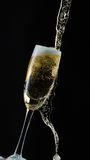Glass of champagne with splash, isolated on black background Stock Image
